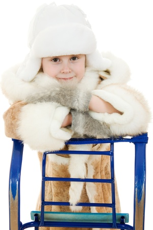 skids: The girl in warm clothes in surprise looking up on white background.