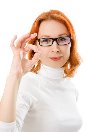 A beautiful girl with red hair wearing glasses shows a gesture ok on a white background. photo