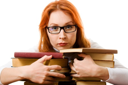 Beautiful red-haired girl in glasses reads book on a white background. photo