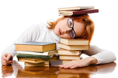 Beautiful red-haired girl in glasses reads book on a white background. Archivio Fotografico