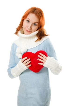 Beautiful girl in warm clothes with a heart on a white background. photo