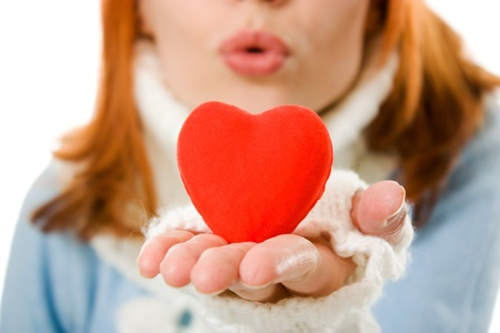 The girl sends an air kiss in the form of heart on a white background. photo