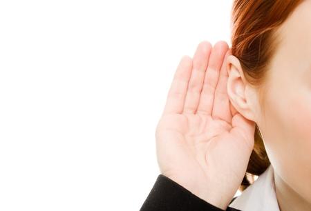 escuchar: Primer plano de la mano de la mujer a la oreja sobre un fondo blanco.