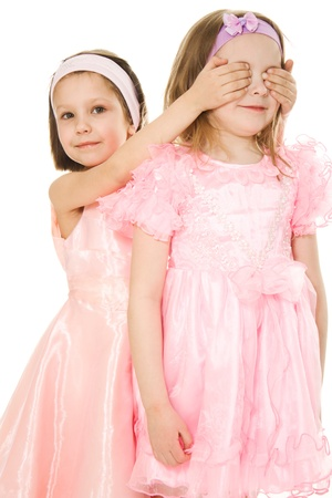 close your eyes: Two friends in pink dresses with his eyes closed his hands on a white background.