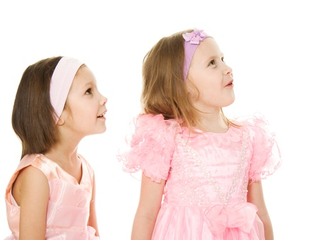 Two friends in a pink dress looking up on a white background. photo