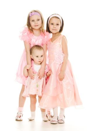 Three girlfriends in pink dresses hug on white background.