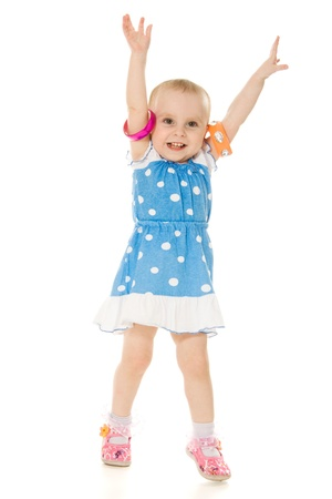 A little girl raised her hands up on a white background.