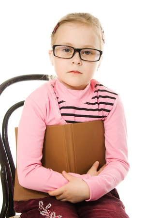 The little girl in glasses with a book on a white background. photo
