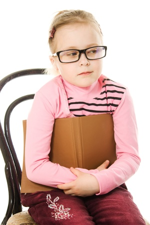 The little girl in glasses with a book on a white background. Stock Photo - 13090303