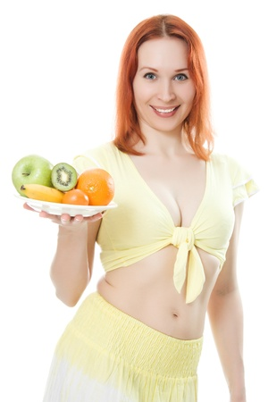 Young woman with fruit on a plate on a white background. photo