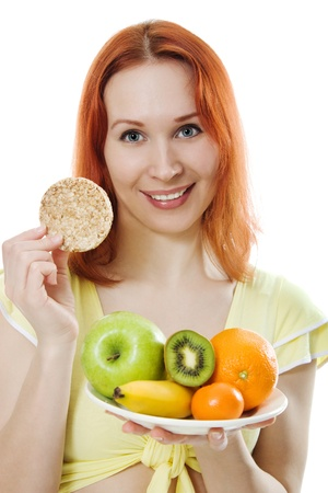 Young woman with fruit on a plate and loaves on a white background. photo