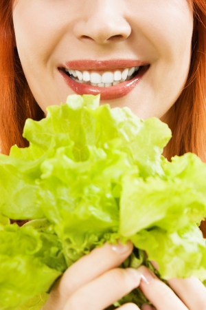 young beautiful  woman eating salad close up photo