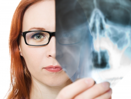 Female doctor examining X-ray image on a white background.