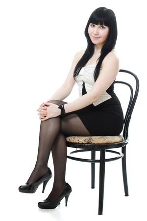personas sentadas: Claro que una mujer hermosa en traje de noche sentado en una silla sobre un fondo blanco
