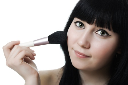 makeup brush: Beautiful woman with makeup brush near her face