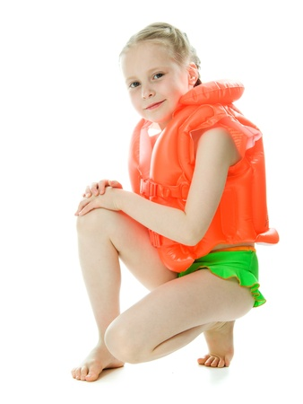 Young girl with yellow lifejacket on a white background. photo
