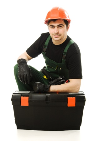Service man wearing helmet and overall holding black toolbox over white photo