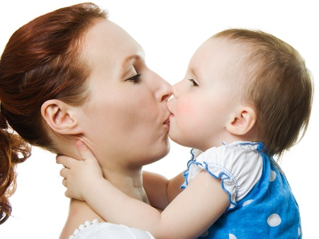 Mother kissing her daughter on a white background photo