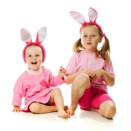 La bambina con le orecchie coniglio rosa su sfondo bianco. photo