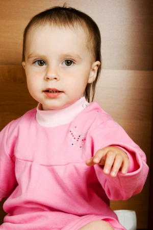 Baby girl in pink dress waving hand photo