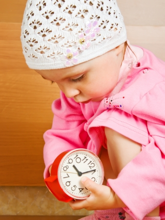 Cute little girl with the clock indoors photo
