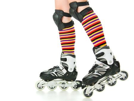 Feminine legs with roller skates on a white background. photo