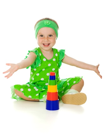 Little girl is playing with toy pyramid on a white background Standard-Bild