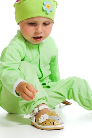 Small child looking at his flip-flops on a white background. photo
