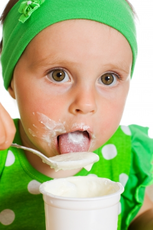 girl eats with a spoon dairy product on a white background. photo