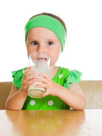 Cute little girl drinking milk from big glass while sitting at table, isolated over white photo