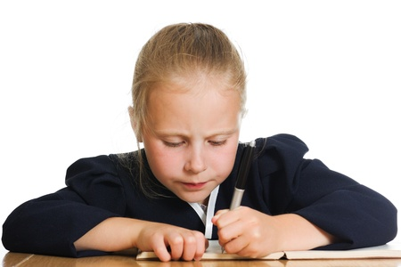 Schoolgirl writes at a table on a white background. photo