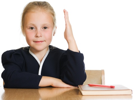 The schoolgirl is sitting at his desk with his hand raised on a white background. photo