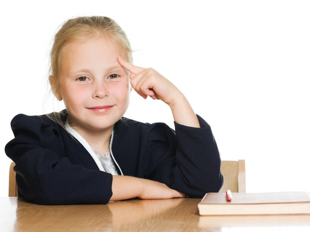 The schoolgirl is sitting at his desk and points the finger at his head on a white background. photo