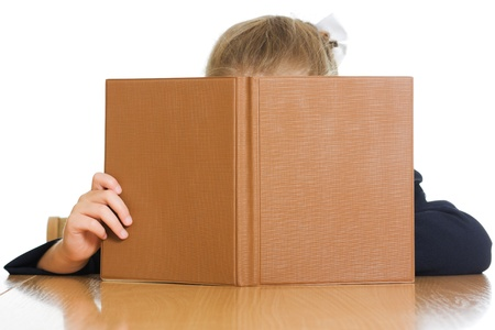 The schoolgirl is hiding behind a book on a white background.