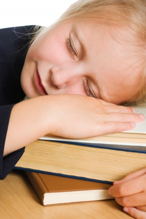 Girl asleep on the books at the table photo