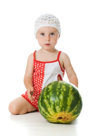 An adorable baby happily plays the watermelon on a white background. photo