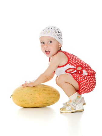 An adorable baby happily playing melon on a white background. photo