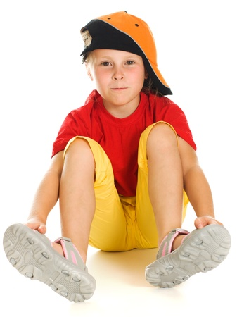 A cheerful little child with funny cap is lying on white background photo