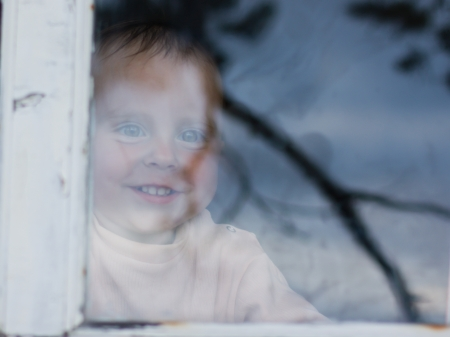 the other side: young baby looking from window on the other side