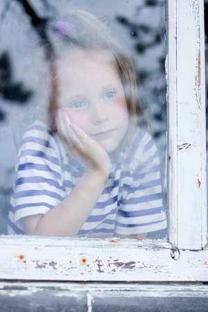 young girl looking from window on the other side photo