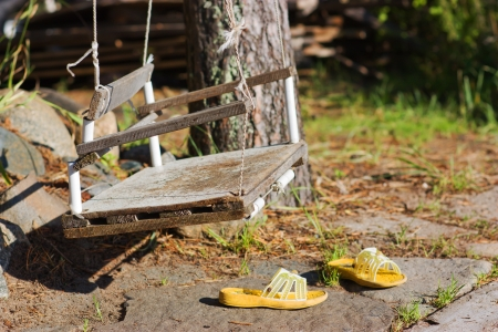 baby swing in garden and slippers photo