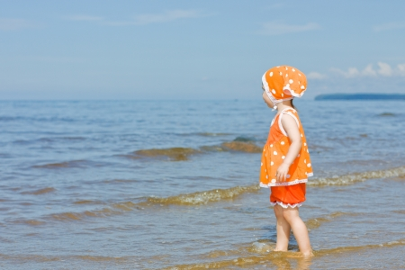 Little baby girl walking on the beach photo