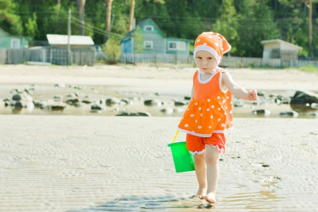 The little girl on the beach is water in the bucket. photo