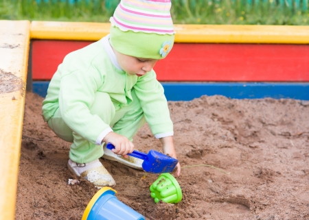 Little kid playing in a sandbox on the playground.