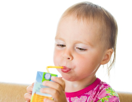 Small beautiful baby drinking juice from straw on a white background. photo