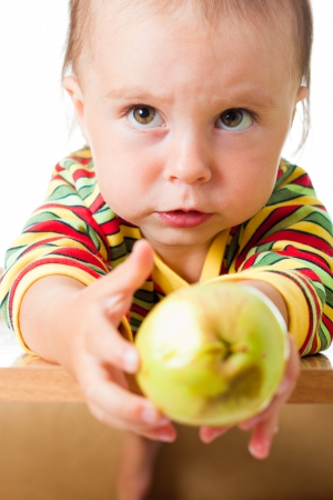 the kid at the table with the rotten apple. Stock Photo - 15288583