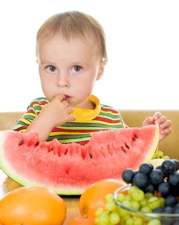 little baby with fruits, close up,  concept of health care and healthy child nutrition photo