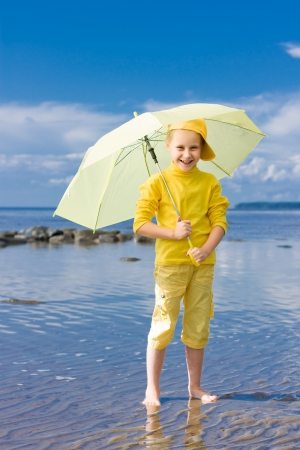 girl with a yellow umbrella on a beach photo
