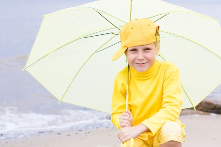 brolly: The girl in yellow clothes with umbrella sitting on the beach.