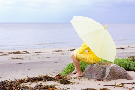 The girl in yellow clothes with umbrella sitting on the beach. photo